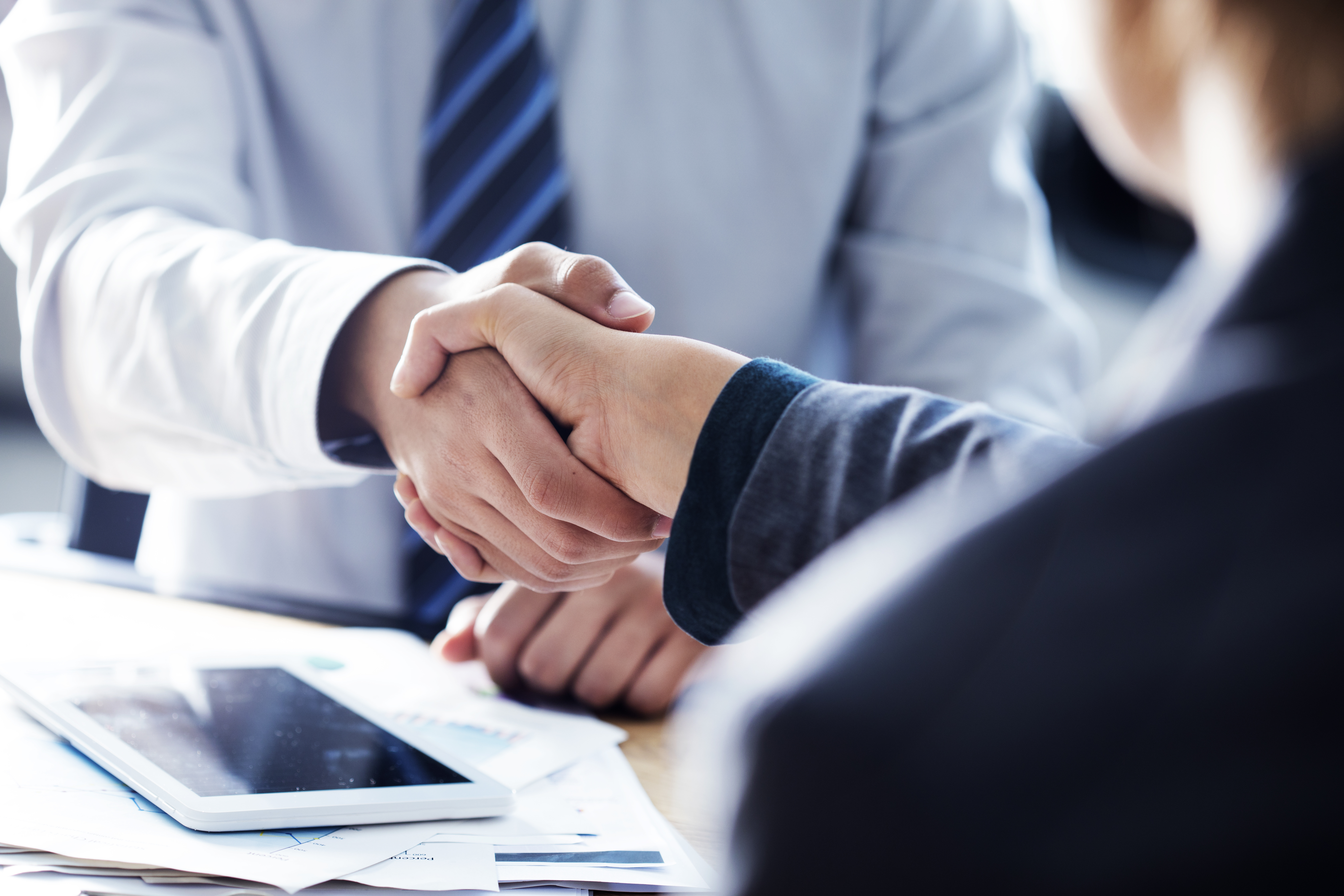 Insurance agent and client shaking hands.
