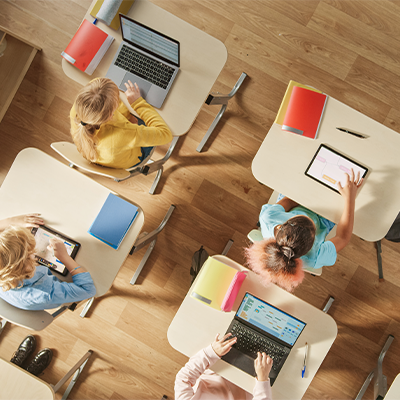 Students sitting at desks using devices.