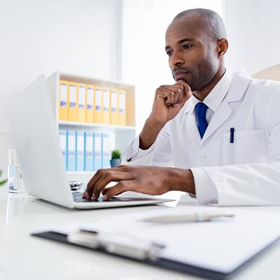 Healthcare worker on laptop.
