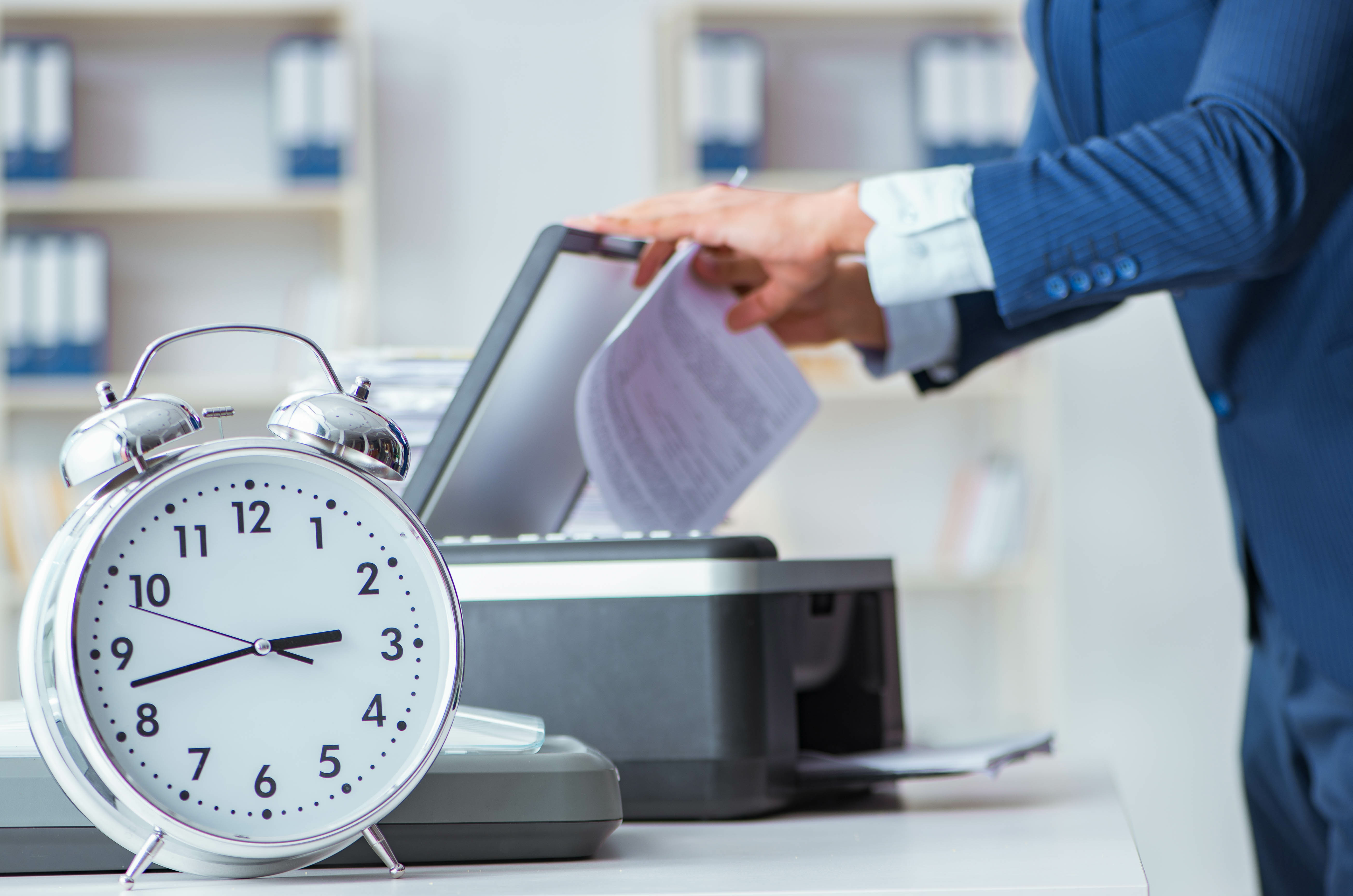 Man using printing with clock in the foreground.